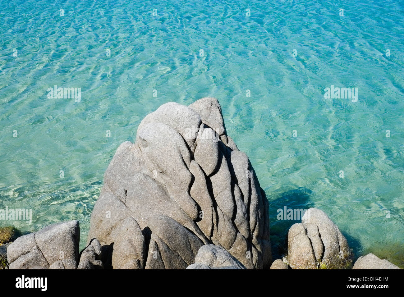 Transparent and green water with rock along the coast in Chia, Sardinia, Italy - Stock Image