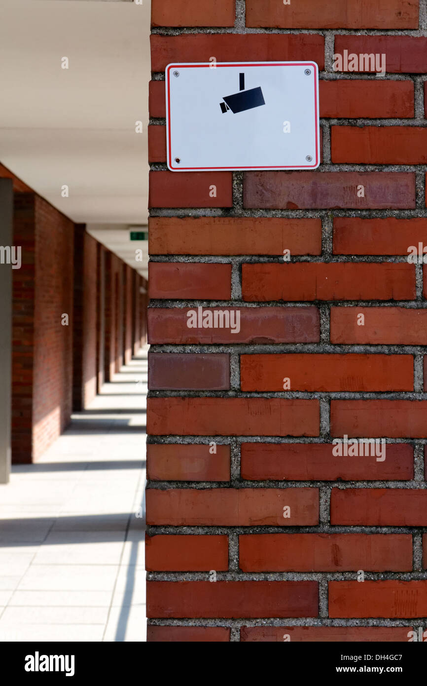 Sign with a camera pictograph warning of video surveillance on a red brick wall. Stock Photo