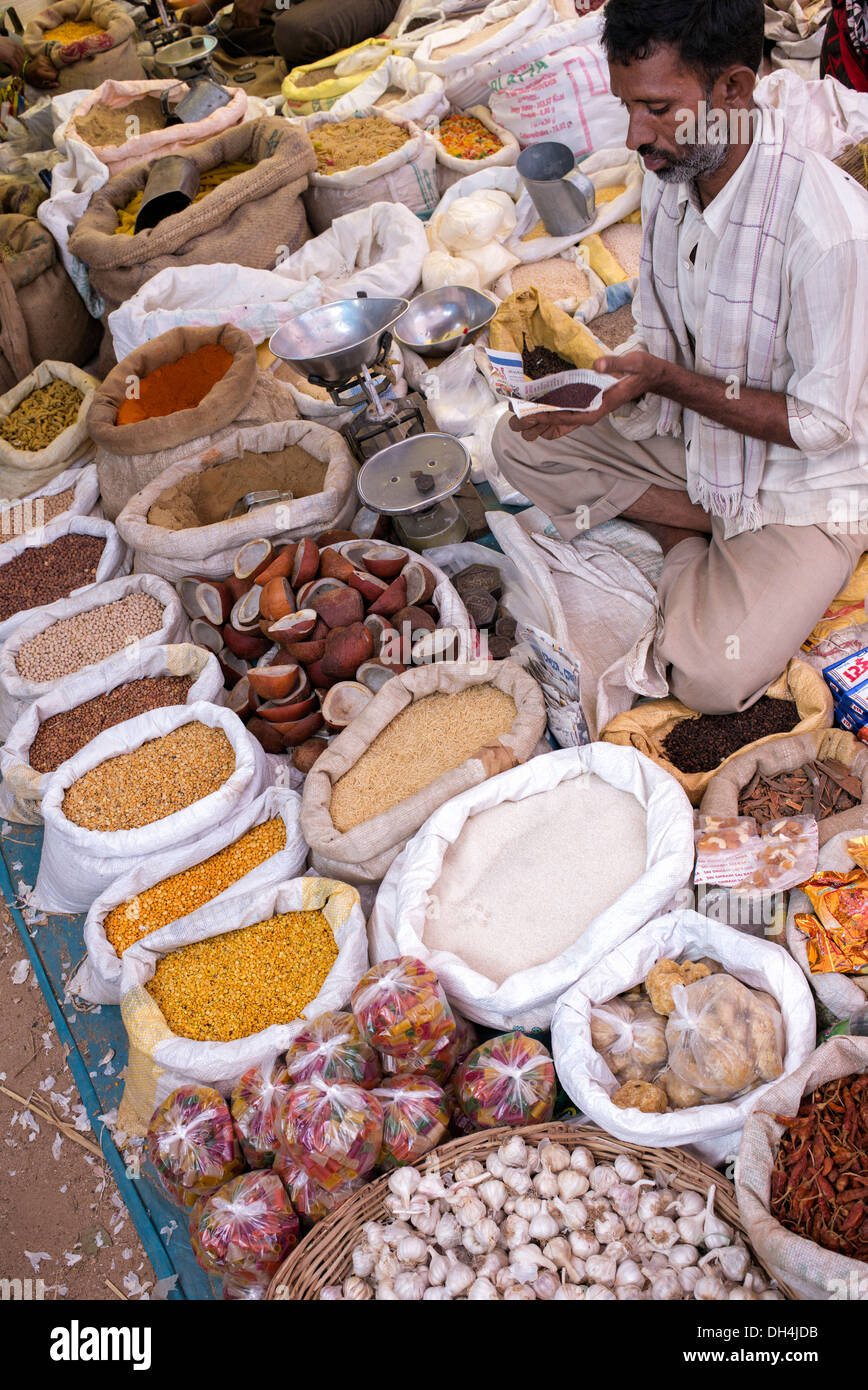 Indian man selling spices and dried produce from sacks at an Indian market. Andhra Pradesh, India - Stock Image