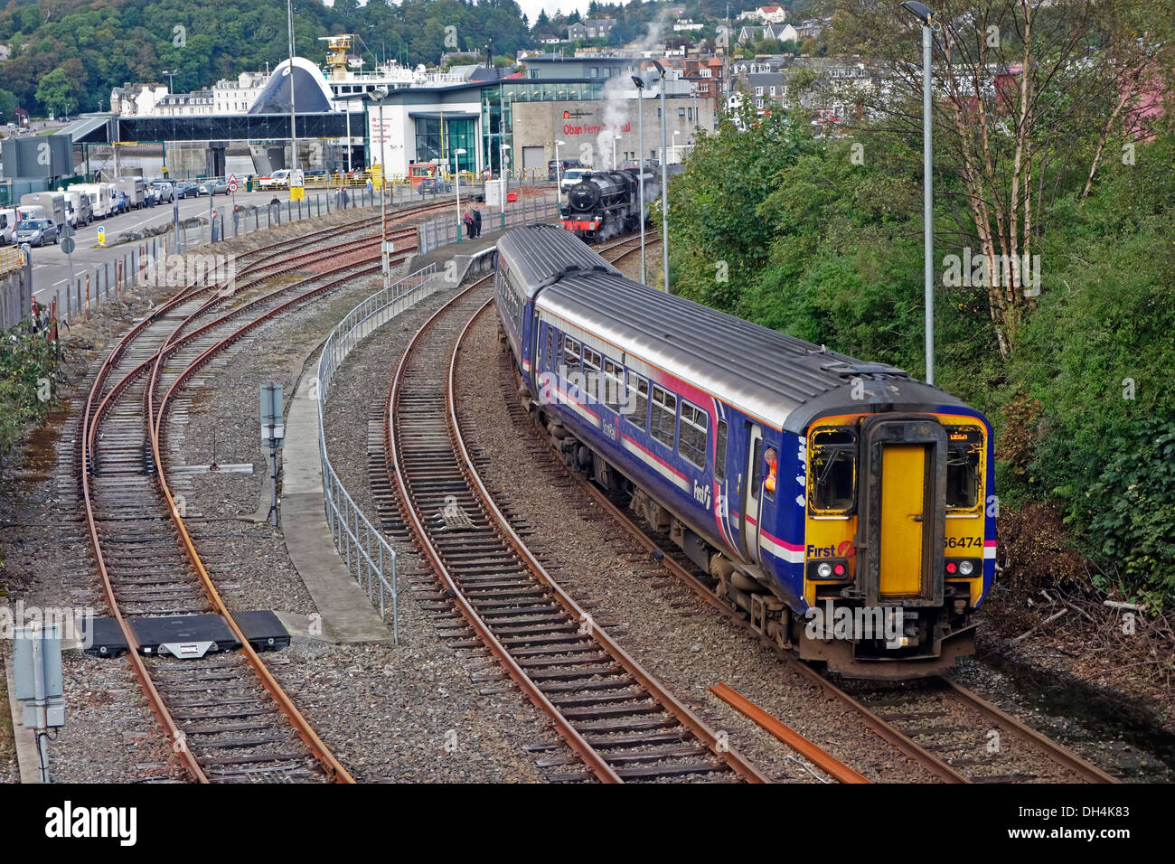 First Scotrail Class 156 DMU arrives at Railway Station in Oban Scotland & steam engine ready to depart with excursion train - Stock Image