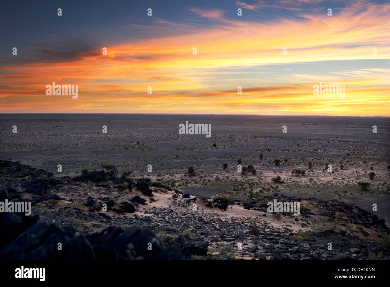 Sun rising with view from granite rocky outcrop in hill location, Western Sahara desert, Mauritania, NW Africa - Stock Image