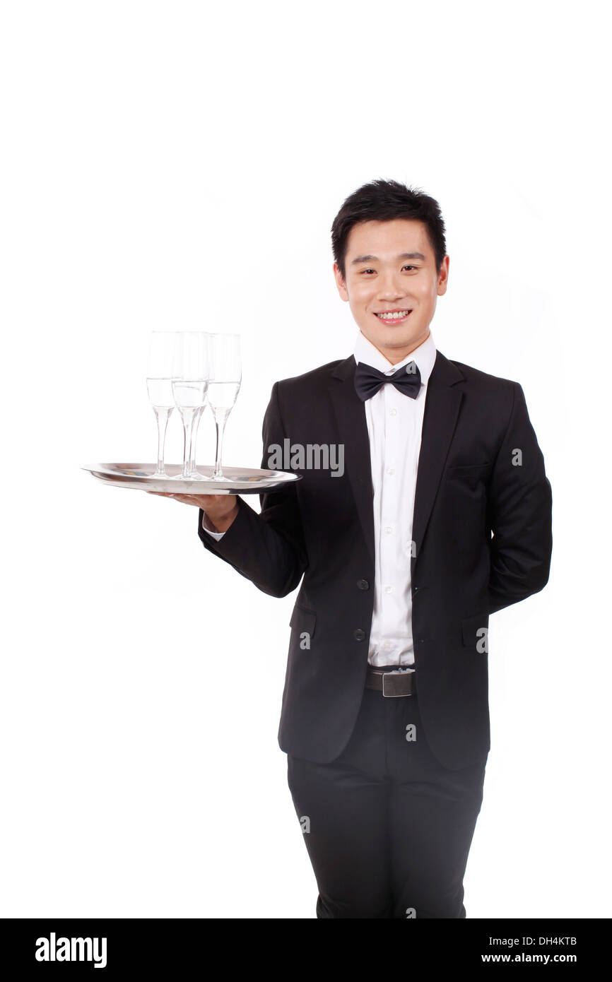 Man in tuxedo holding a plate - Stock Image