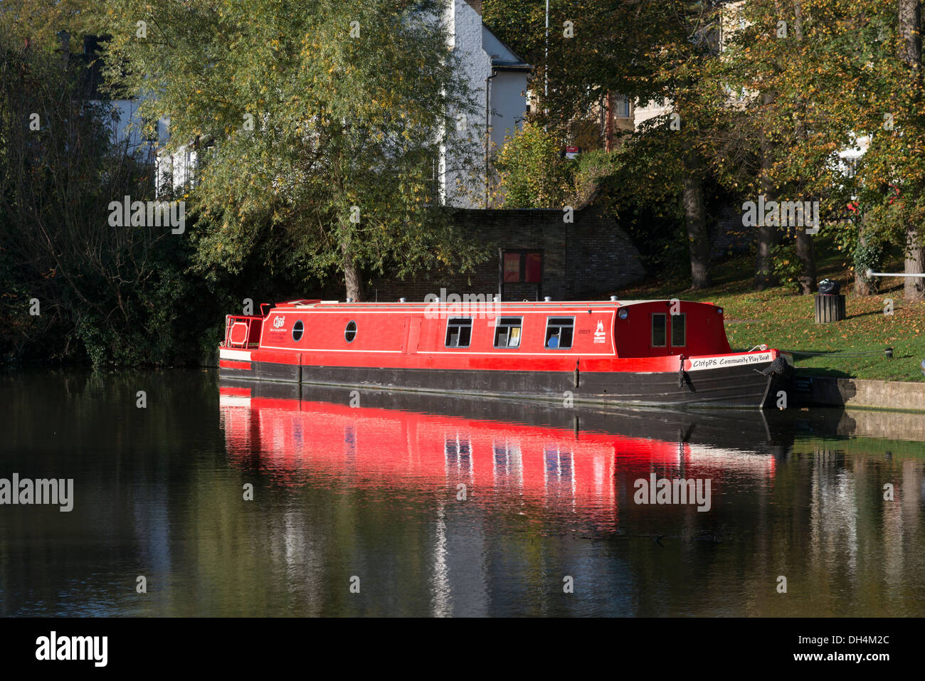 A red longboat or narrowboat moored on the River Cam Cambridge UK - Stock Image