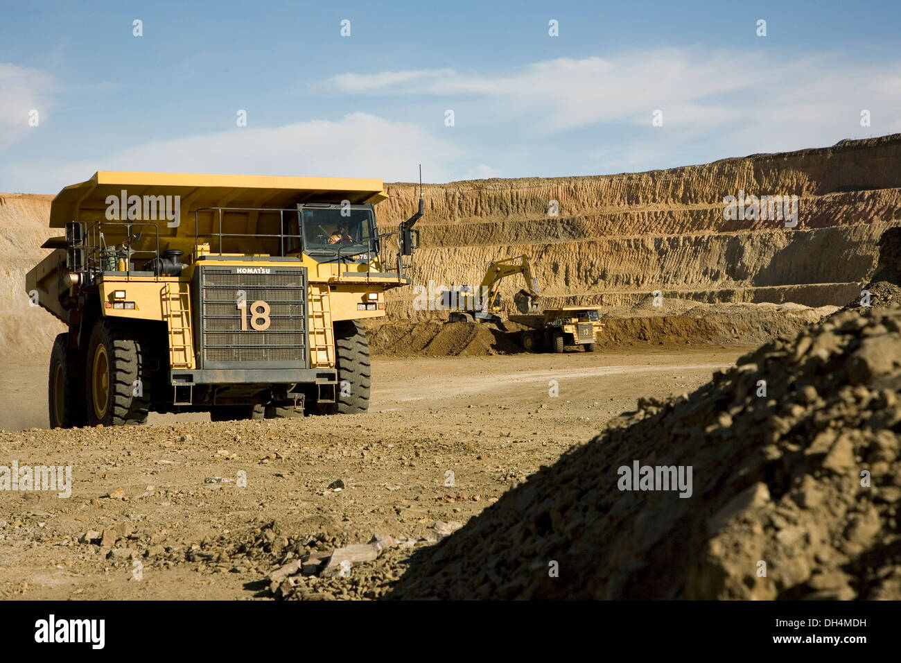 Gold mine operation in open cast surface pit with large haul truck leaving and excavators working behind, Mauritania, - Stock Image