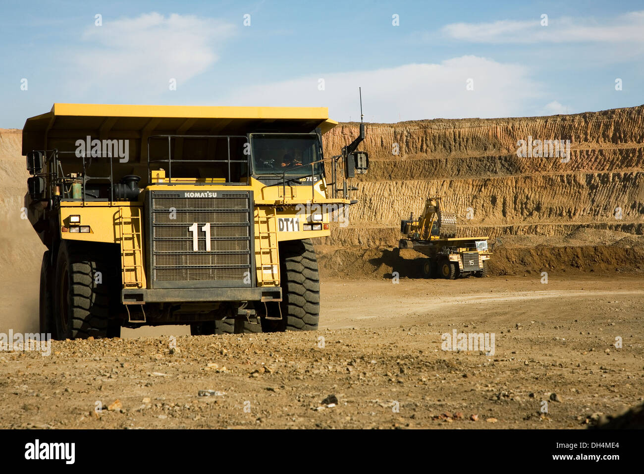 Gold mine operation in open cast surface pit with large haul truck leaving and excavators working behind, Mauritania, NW Africa - Stock Image