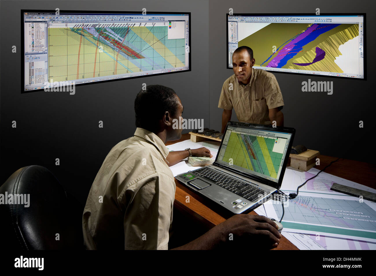 Exploration geologists discussing cross section showing stratigraphy of rocks and resource modeling in office, mining project - Stock Image