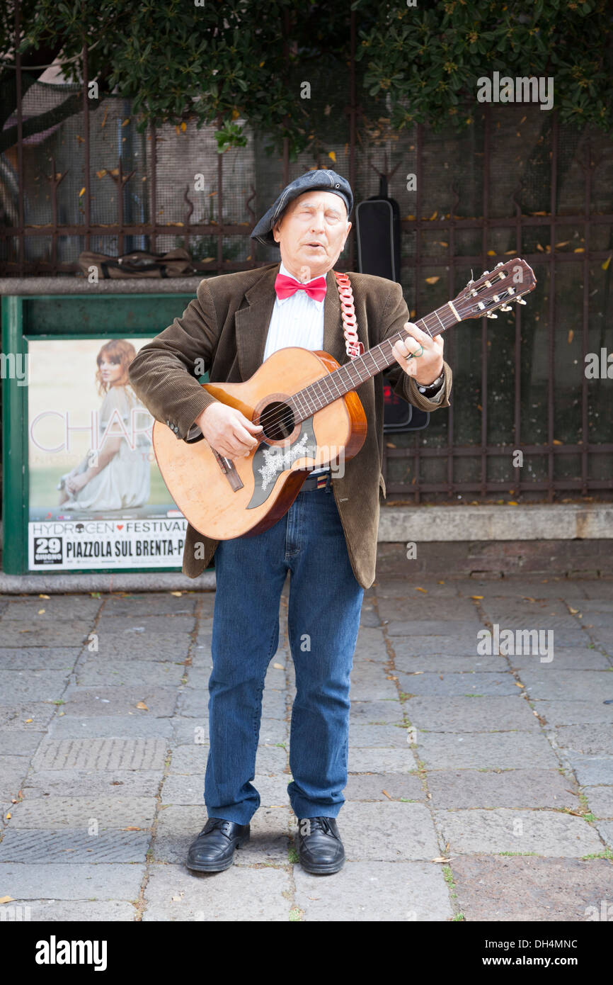 A street singer performing at St Rocco Square near the eponymous church and the Big School (Venice - Italy). Chanteur des rues. - Stock Image