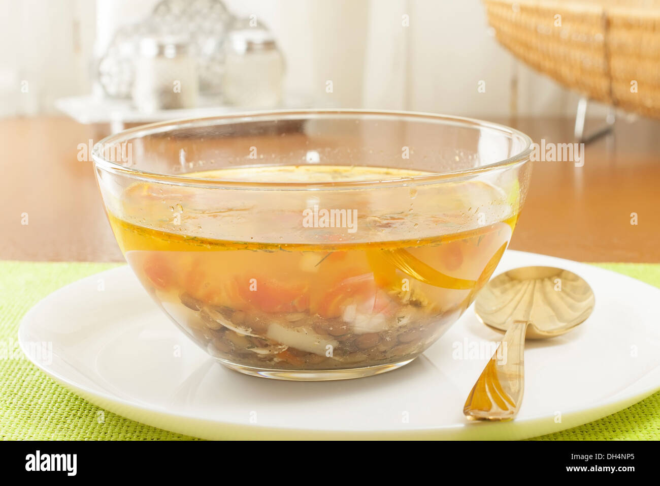 transparent lentil soup in a glass dish - Stock Image
