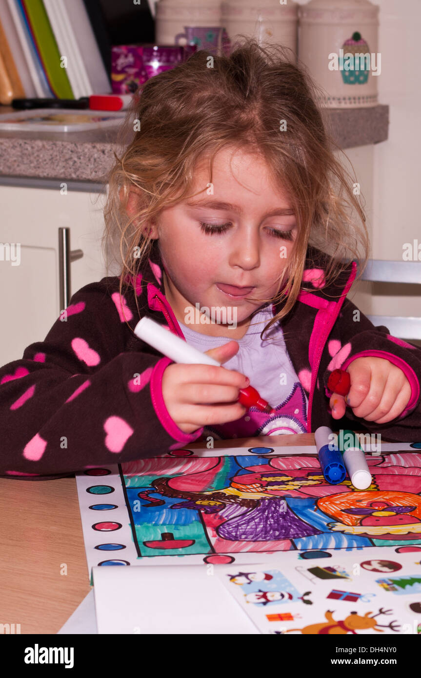 5 Year Old Girl Colouring A Picture In A Colouring Book Stock