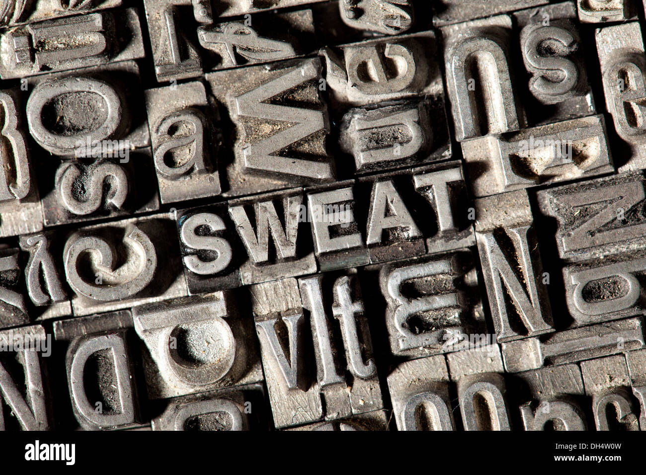 Old lead letters forming the word 'SWEAT' - Stock Image
