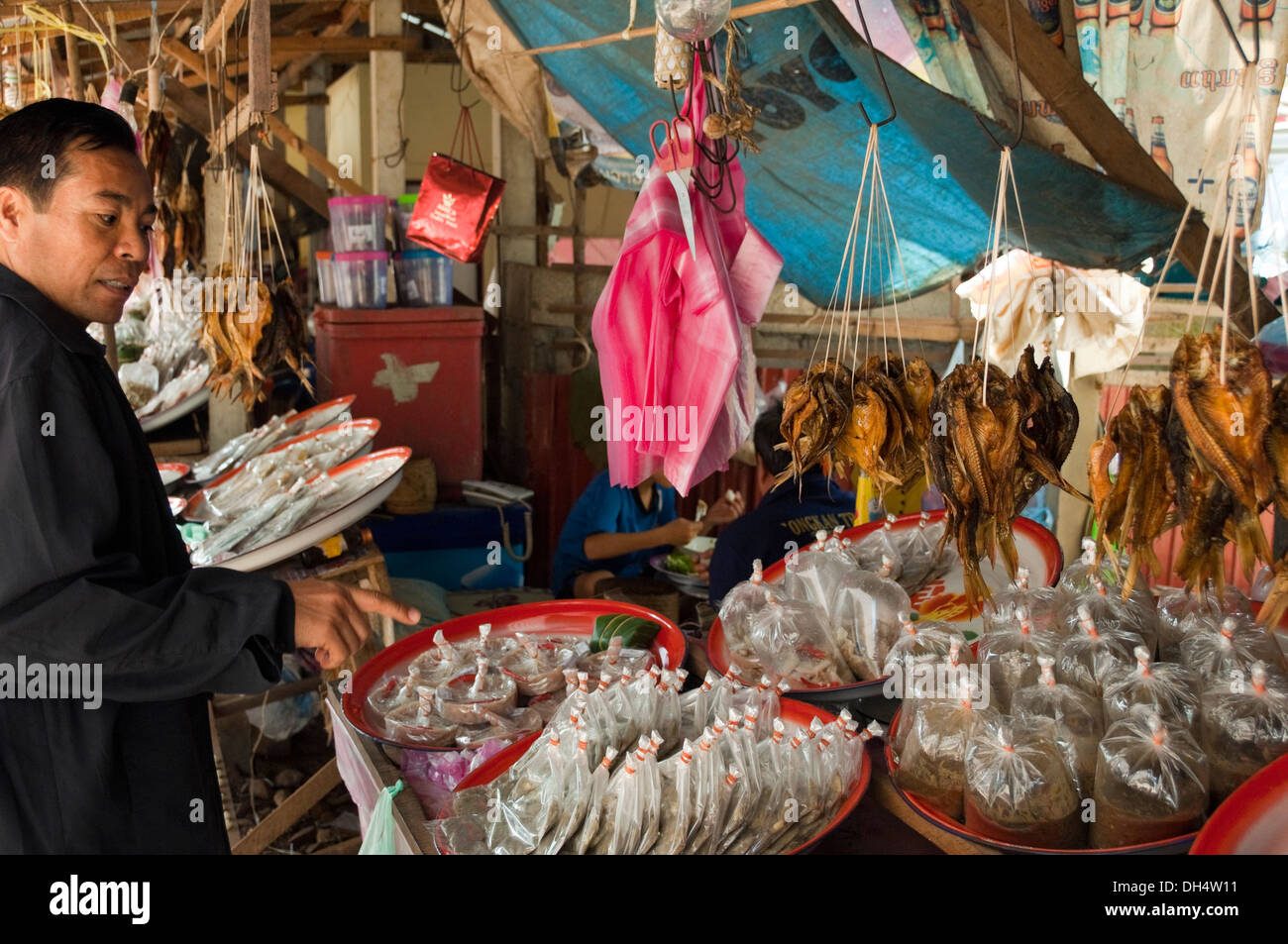 Horizontal portrait of a local Lao man deciding what to buy at a food market in Laos. - Stock Image