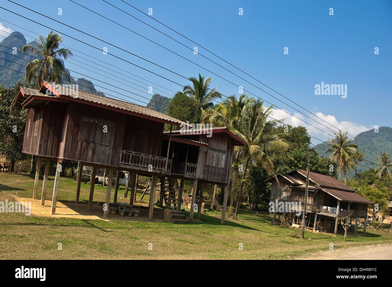 Horizontal view of traditional stilted wooden houses along a countryside street in Laos. Stock Photo