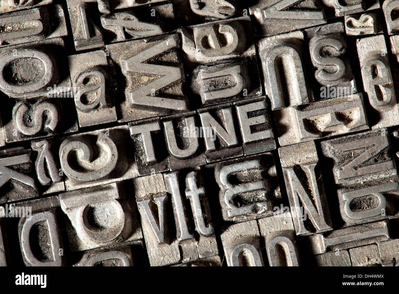 Old lead letters forming the word TUNE - Stock Image