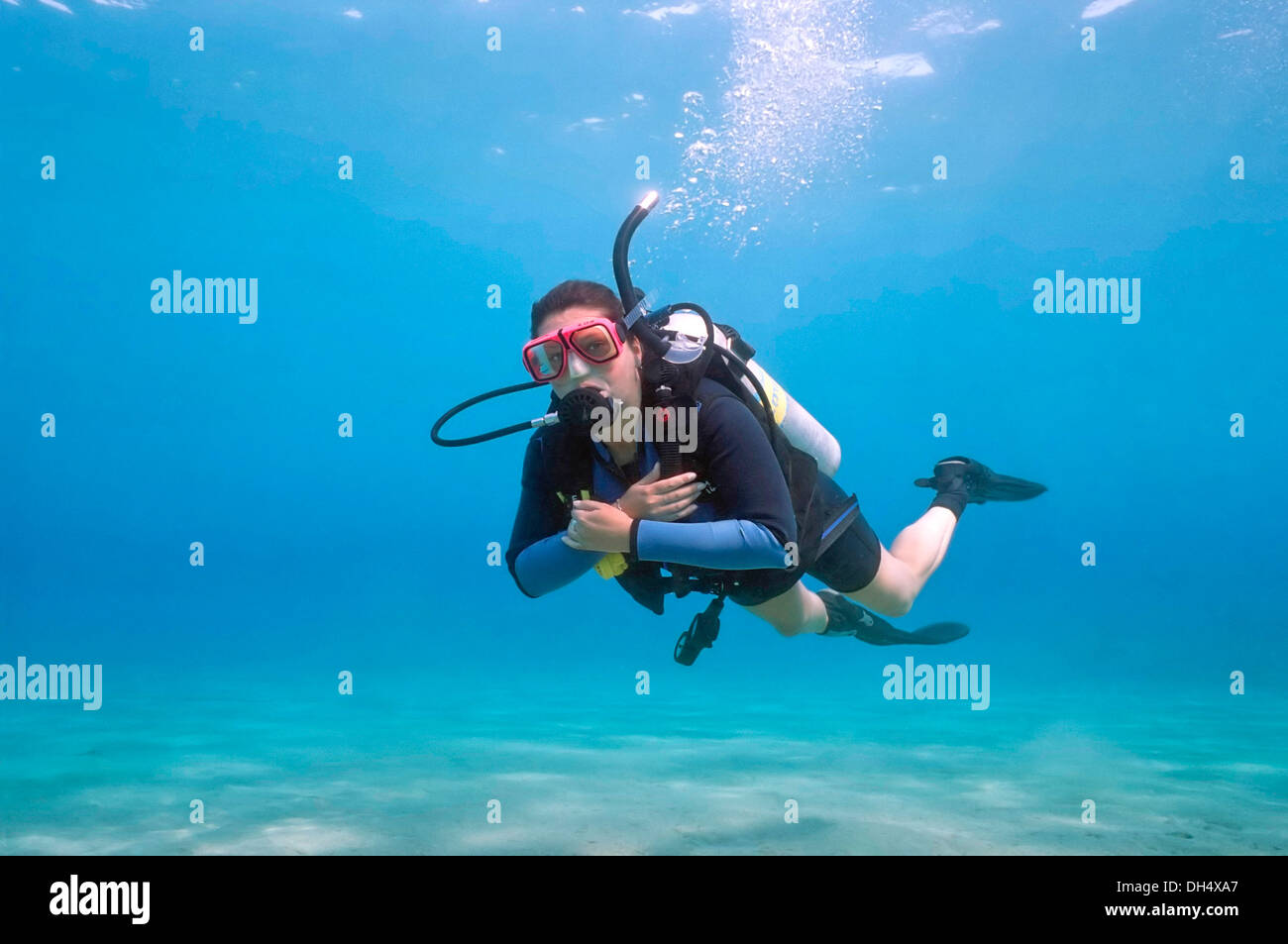 Horizontal portrait of a woman scuba diving in the sea. - Stock Image