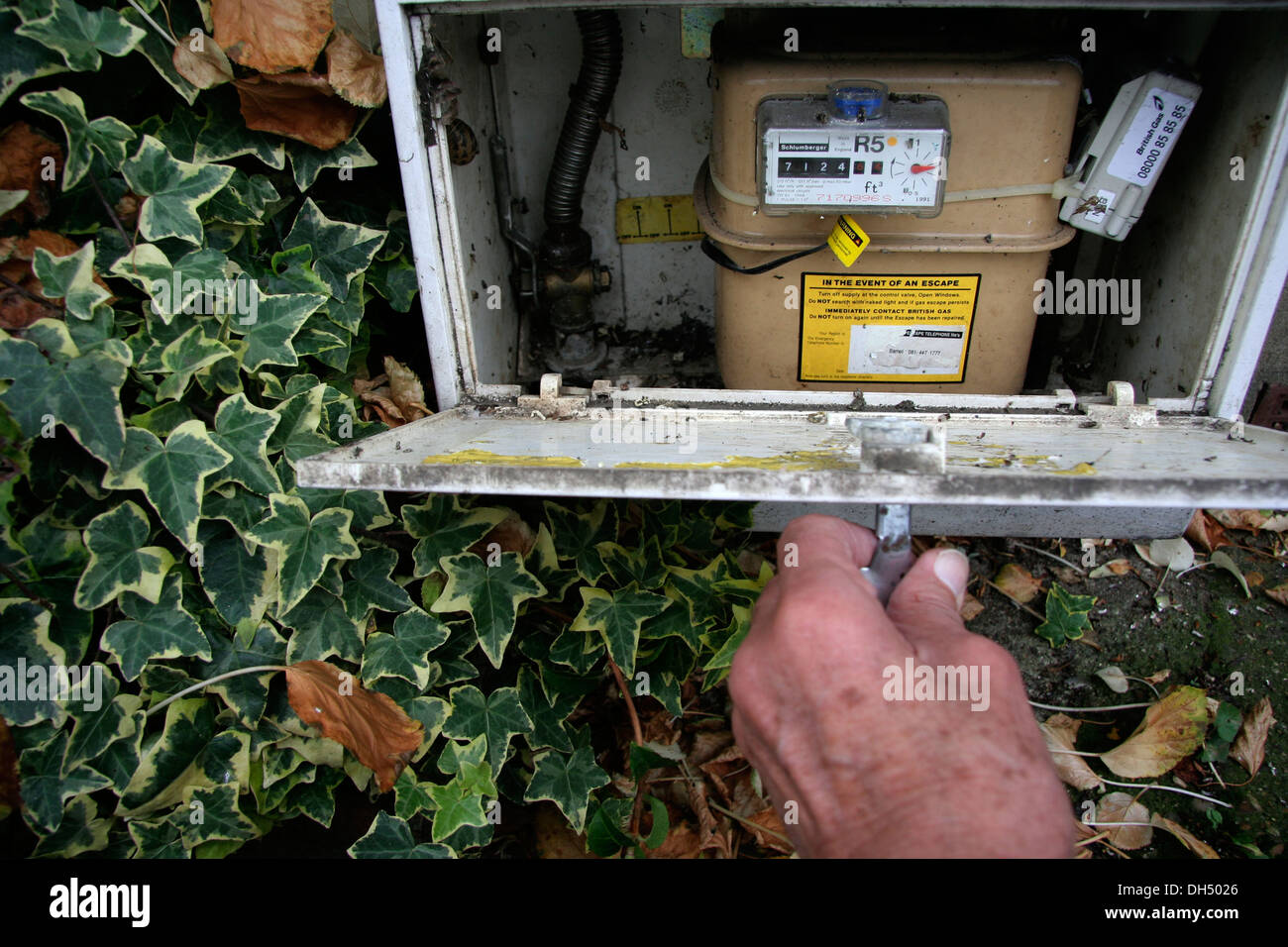 A uk gas meter being read during the Autumn Period - Stock Image