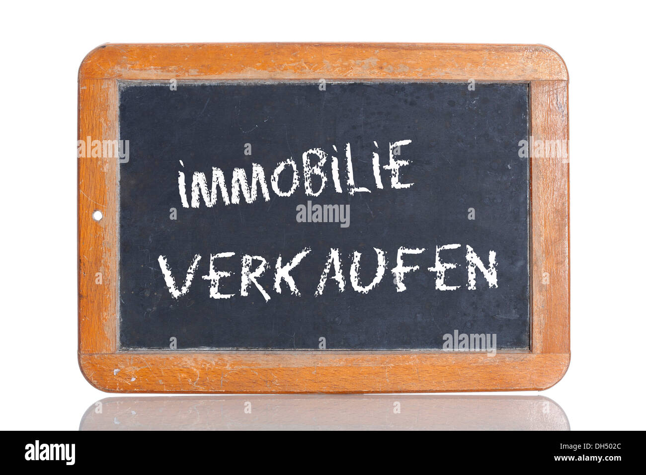 Old chalkboard, lettering 'IMMOBILIE VERKAUFEN', German for 'SELL A PROPERTY' - Stock Image