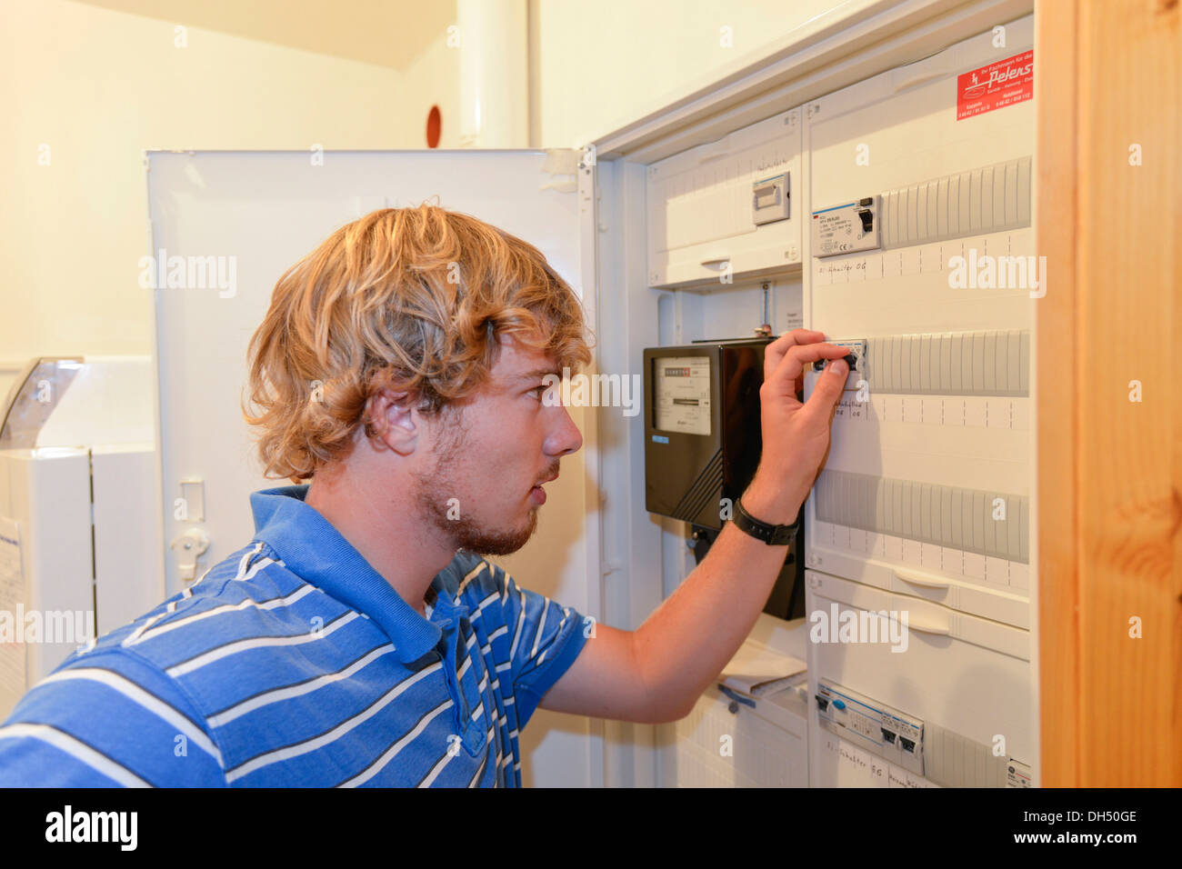 Young man turning off a fuse in a fuse box - Stock Image