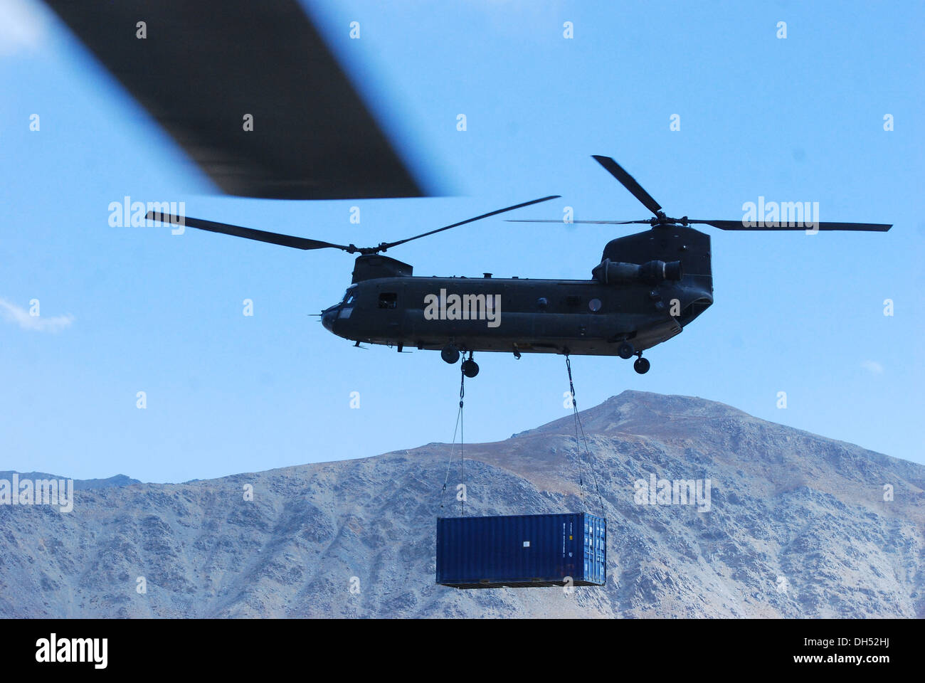 A 10th Combat Aviation Brigade CH-47 Chinook helicopter sling loads a shipping container beneath the belly of the aircraft, Oct. 26, over Wardak province, Afghanistan, as the rotor blade from its sister aircraft is seen out the crew chief's door. 10th Com - Stock Image