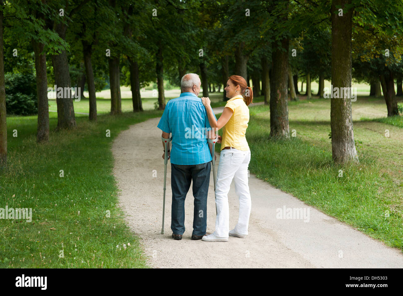 Woman and an elderly man on crutches strolling in the park - Stock Image