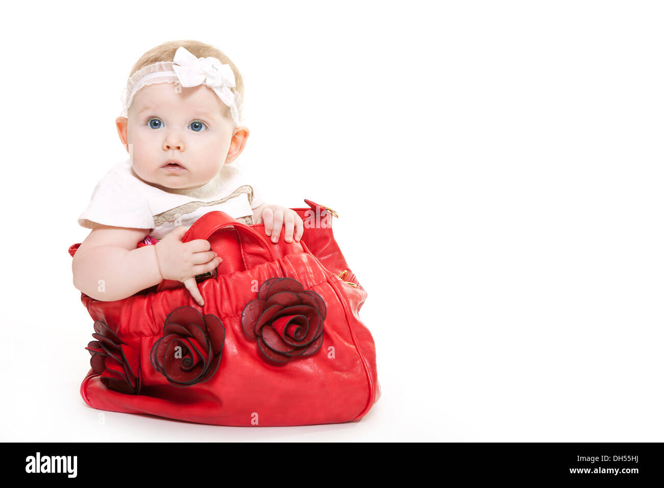 Baby girl sitting in red bag with background from Christmas gift ...