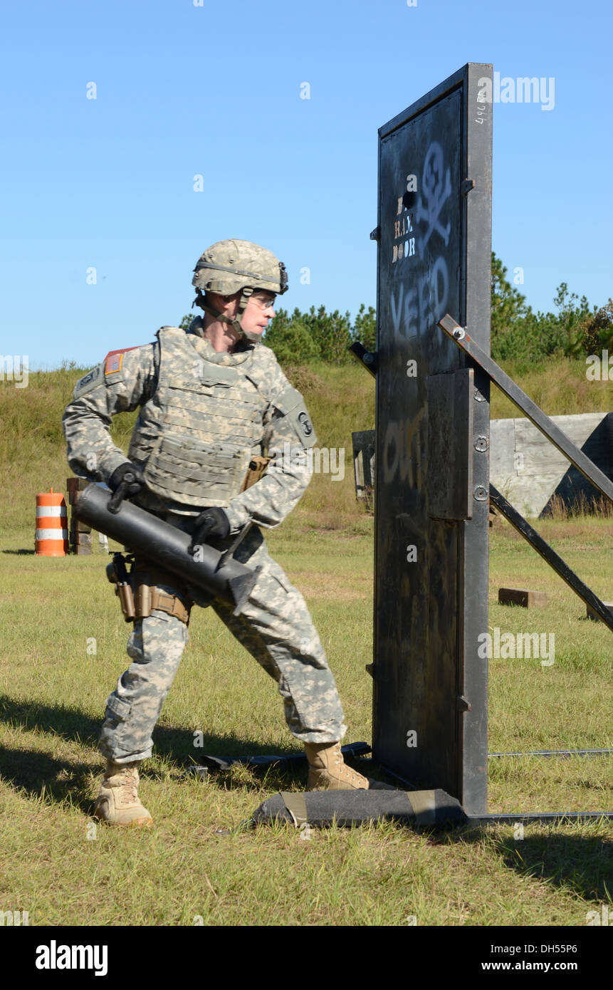 Sgt. Zachery M. Pryor of Litchfield, Ill. breeches a door as part of the challenge trying out for a position on the Fort Bragg Special Reaction Team here Oct. 24, 2013. The challenge includes an Army physical fitness test, an obstacle course, an obstacle - Stock Image