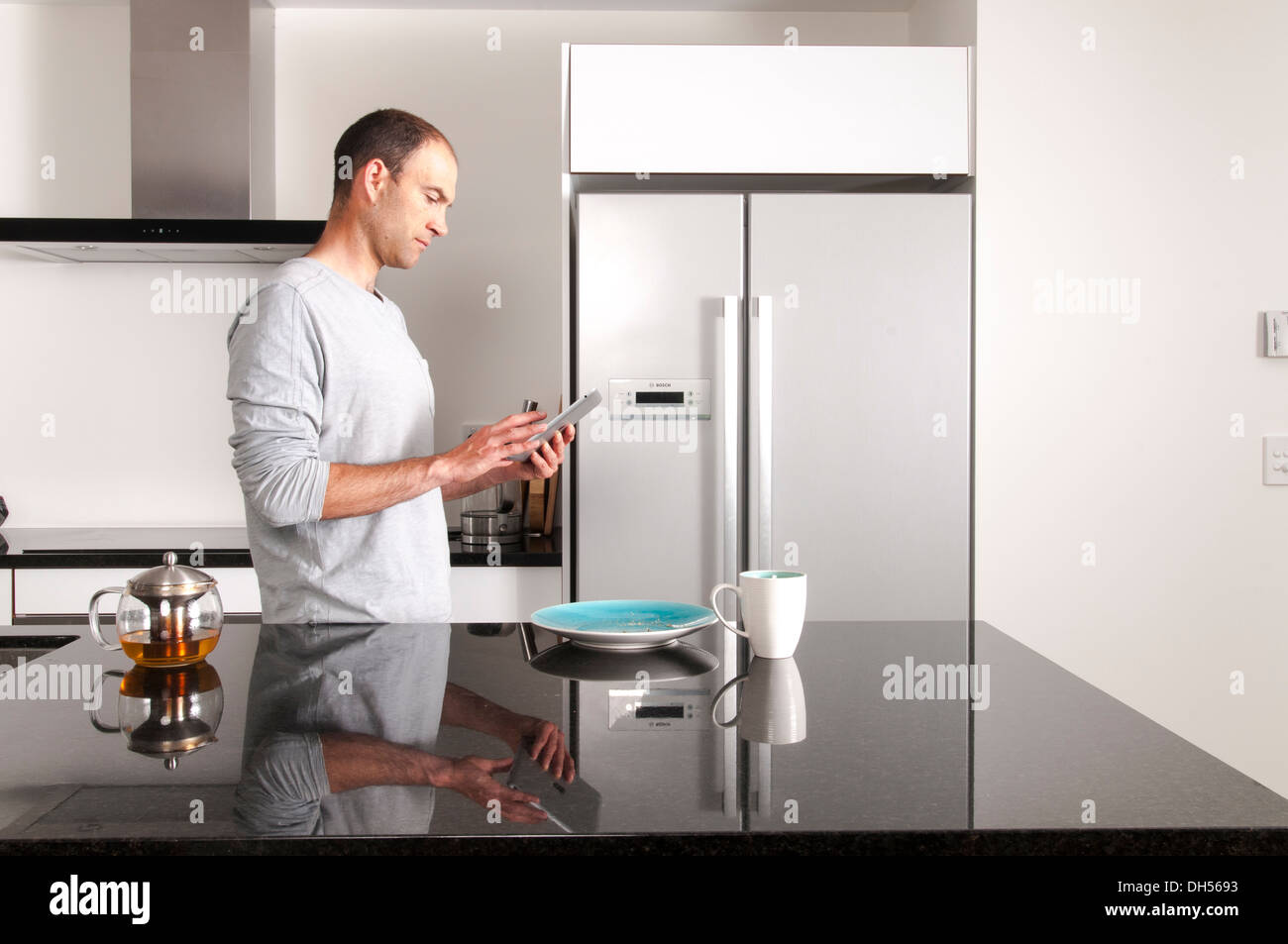 man holding ipad in modern kitchen with cup of green tea and plate ...