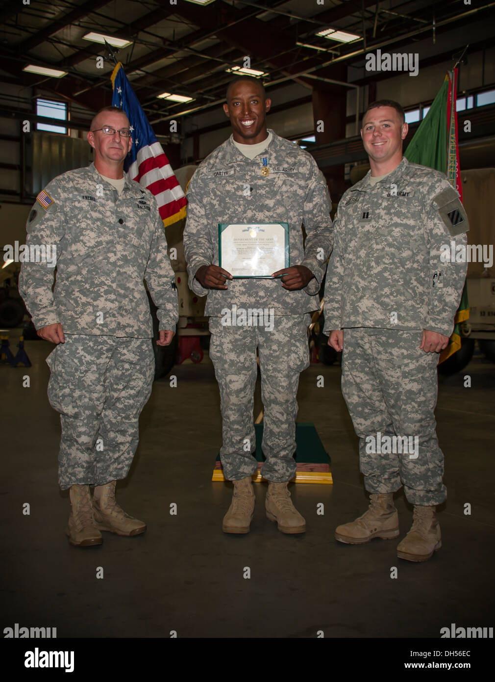 Lt. Col. Rodger Knedel (left), commander, 2-3 Brigade Special Troops Battalion 'Titans', 2nd Armored Brigade Combat Team, 3rd Infantry Division, and Capt. Michael Peters, a company commander for 2-3 BSTB, have a picture taken with Spc. Marquise Carter, mi - Stock Image