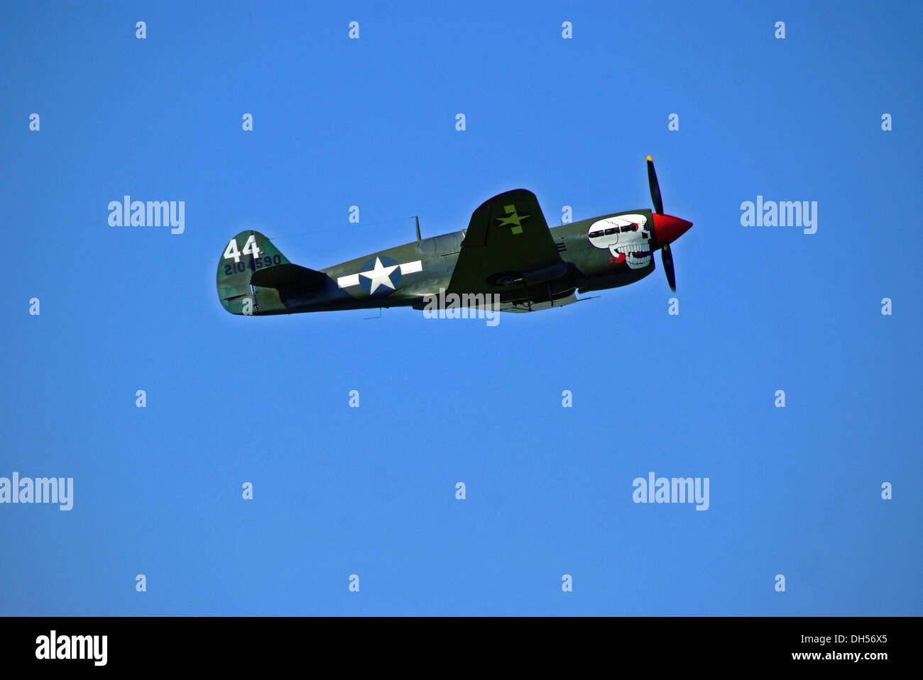 P-40 Curtiss Kittyhawk Flying Against Clear Blue Sky at Sywell Piston and Props Show - Stock Image