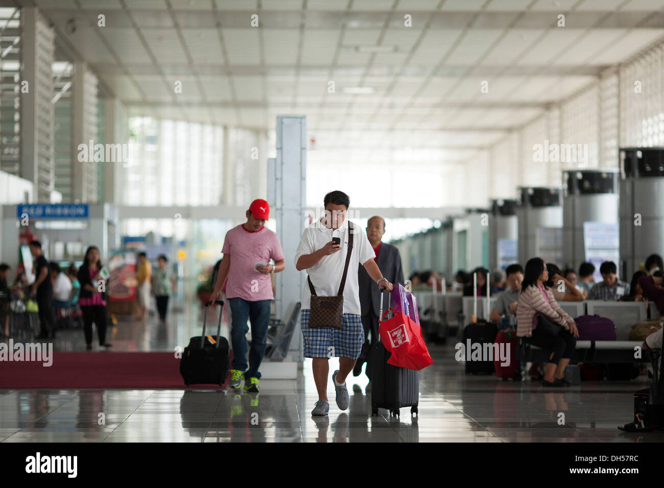 Travelers walk to their gates at Ninoy Aquino International Airport's Terminal 2 in Manila, Philippines. - Stock Image