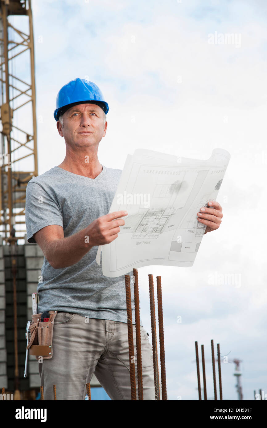 Construction worker wearing a hard hat and holding a building plan, Mannheim, Baden-Württemberg, Germany - Stock Image