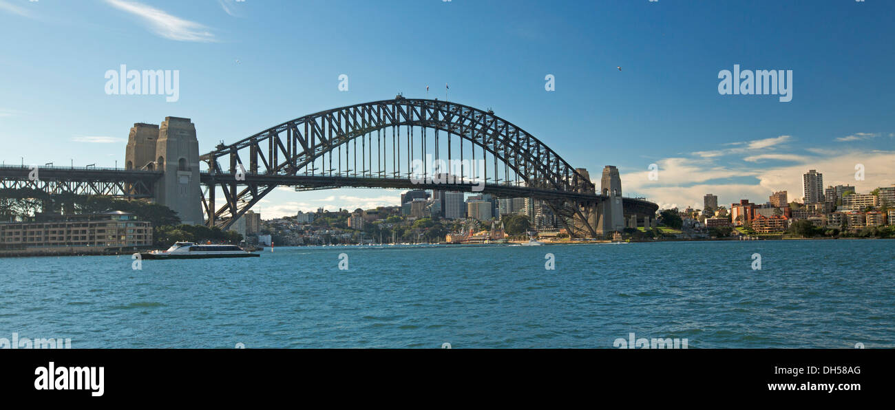 Panoramic view of iconic Sydney harbour bridge spanning calm sapphire blue waters of Darling Harbour in capital city of NSW Australia - Stock Image