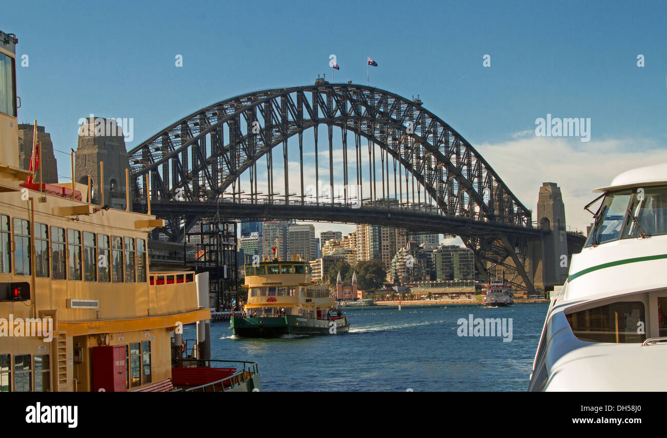 Sydney harbour bridge over blue waters of Darling Harbour with commuter ferry passing by and viewed from among other ferries - Stock Image