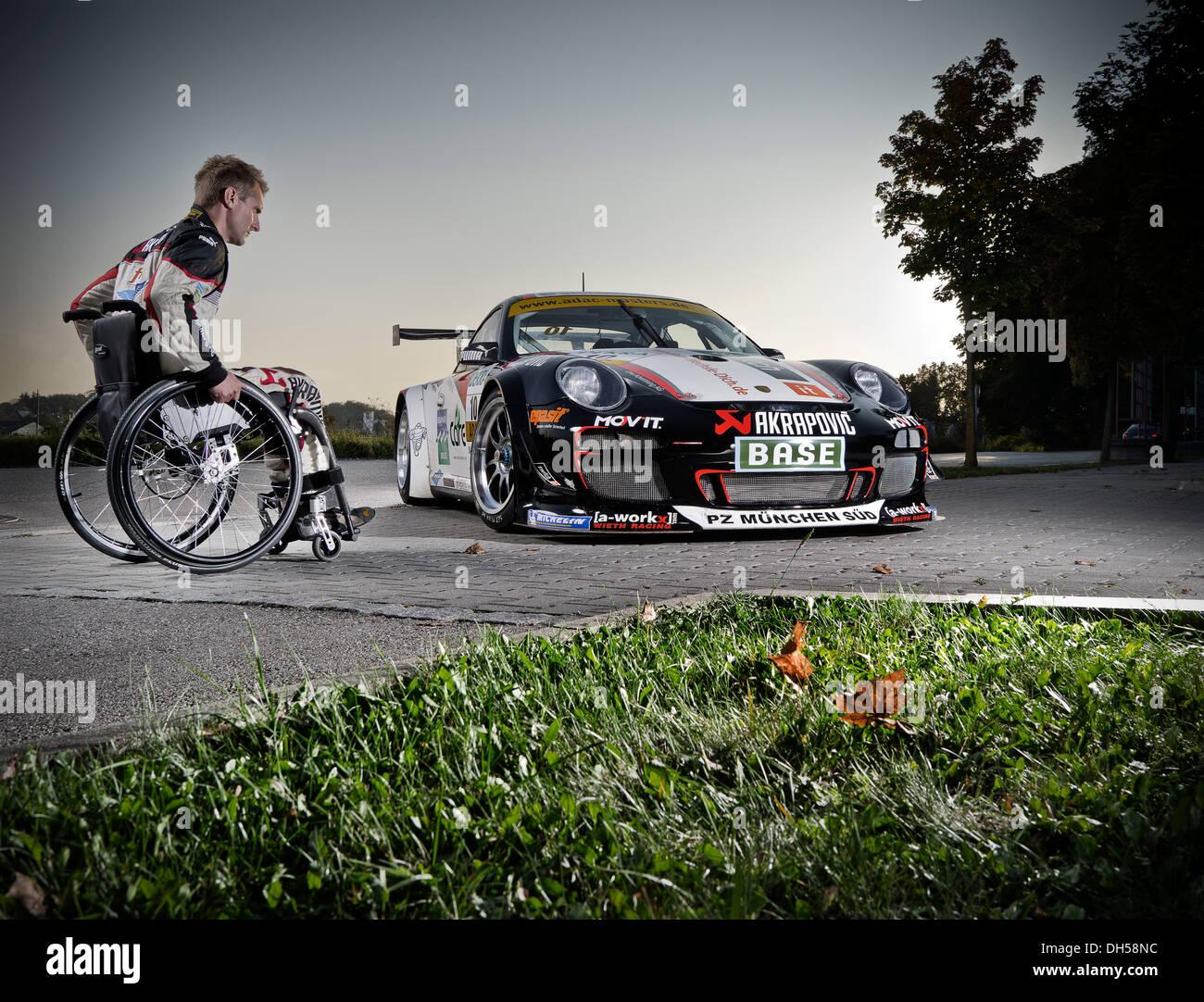 Race car driver in a wheelchair, next to his Porsche race car, Munich, Upper Bavaria, Bavaria, Germany - Stock Image