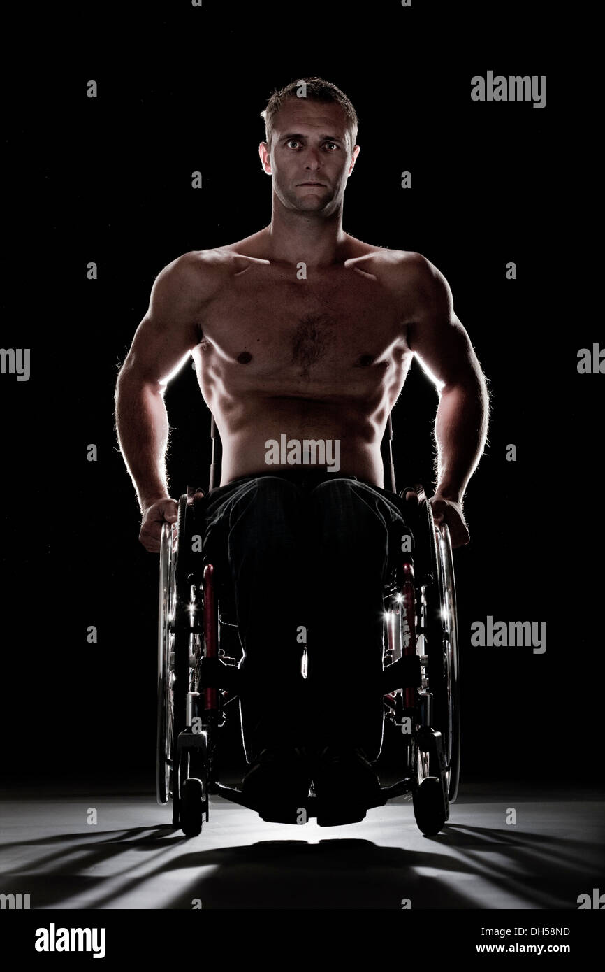 Muscular wheelchair user with a bare chest, feeling uneasy, Innsbruck, Tyrol, Austria - Stock Image