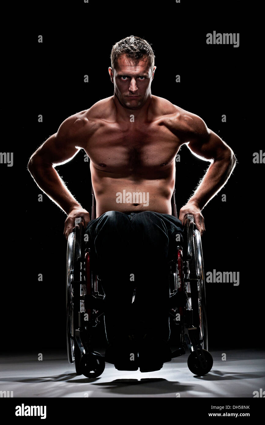 Muscular wheelchair user with a bare chest, Innsbruck, Tyrol, Austria - Stock Image