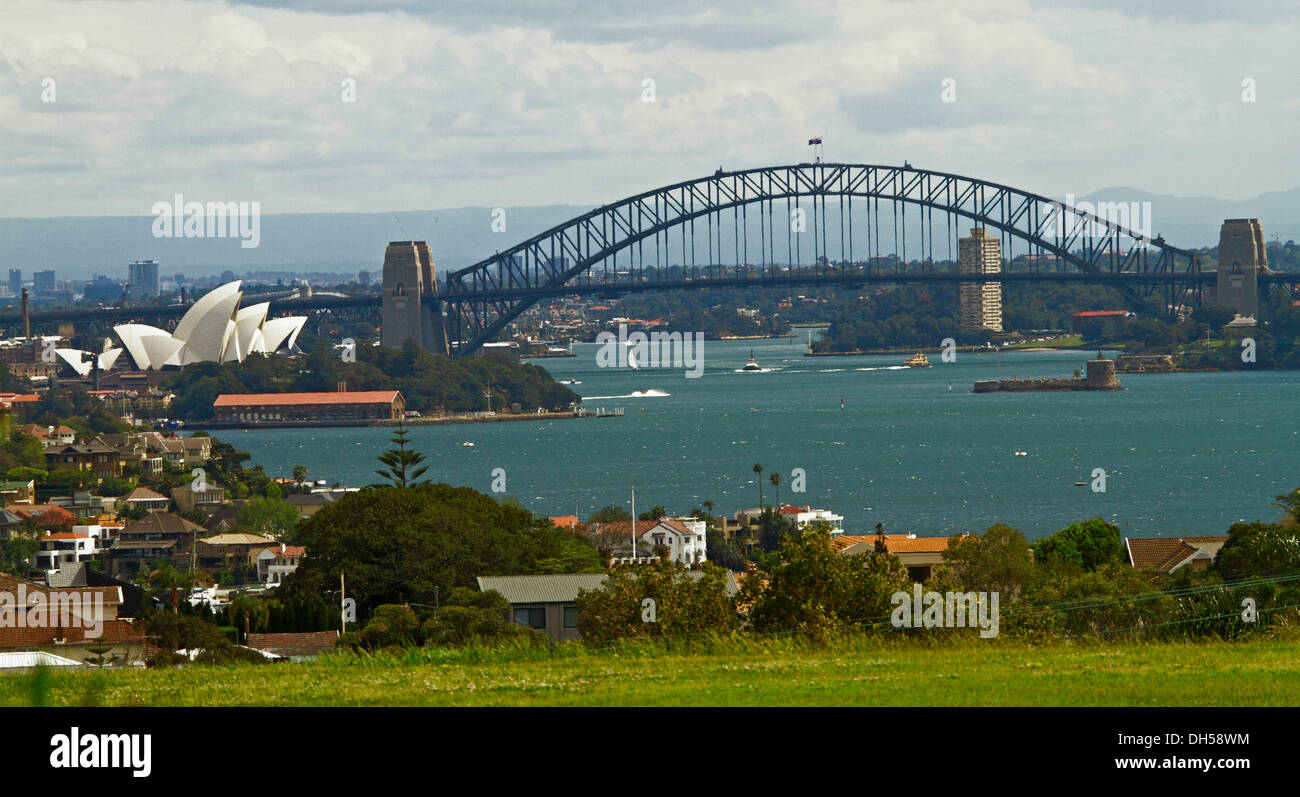 City landscape showing Sydney harbour bridge, iconic opera house, and houses beside blue waters of Darling Harbour - Stock Image