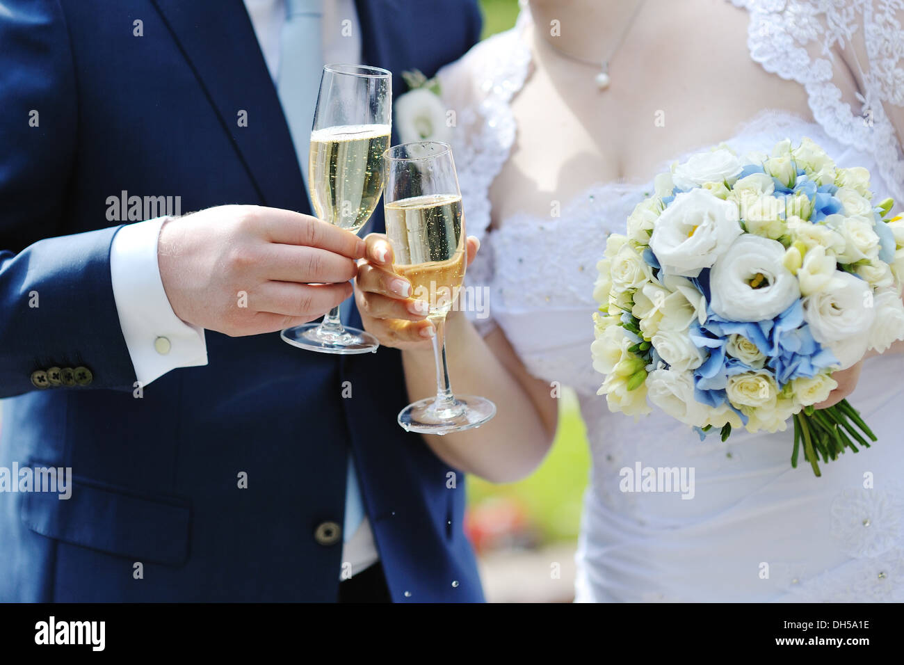 Bride and groom making a toast with champagne glasses after wedding ceremony - Stock Image