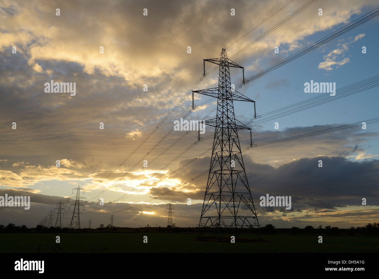 Evening sun setting behind electricity pylons UK - Stock Image