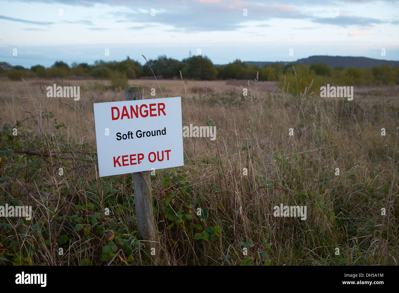 Danger Soft Ground Keep Out sign alongside an area of overgrown land - Stock Image