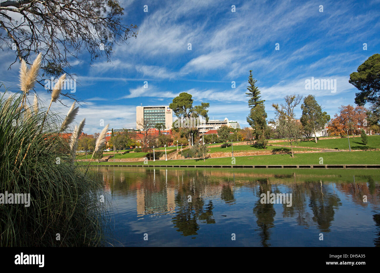 Urban landscape of parklands and Torrens River / Lake in Adelaide with city buildings and trees reflected in calm blue water - Stock Image