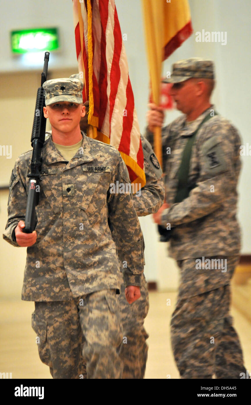 Spc. Colin Bucko, paralegal specialist, 143d Sustainment Command (Expeditionary), leads the color guard off-stage during the closing of the RIP/TOA ceremony. The color guard contained members of both the 143d ESC and the 135th ESC. - Stock Image
