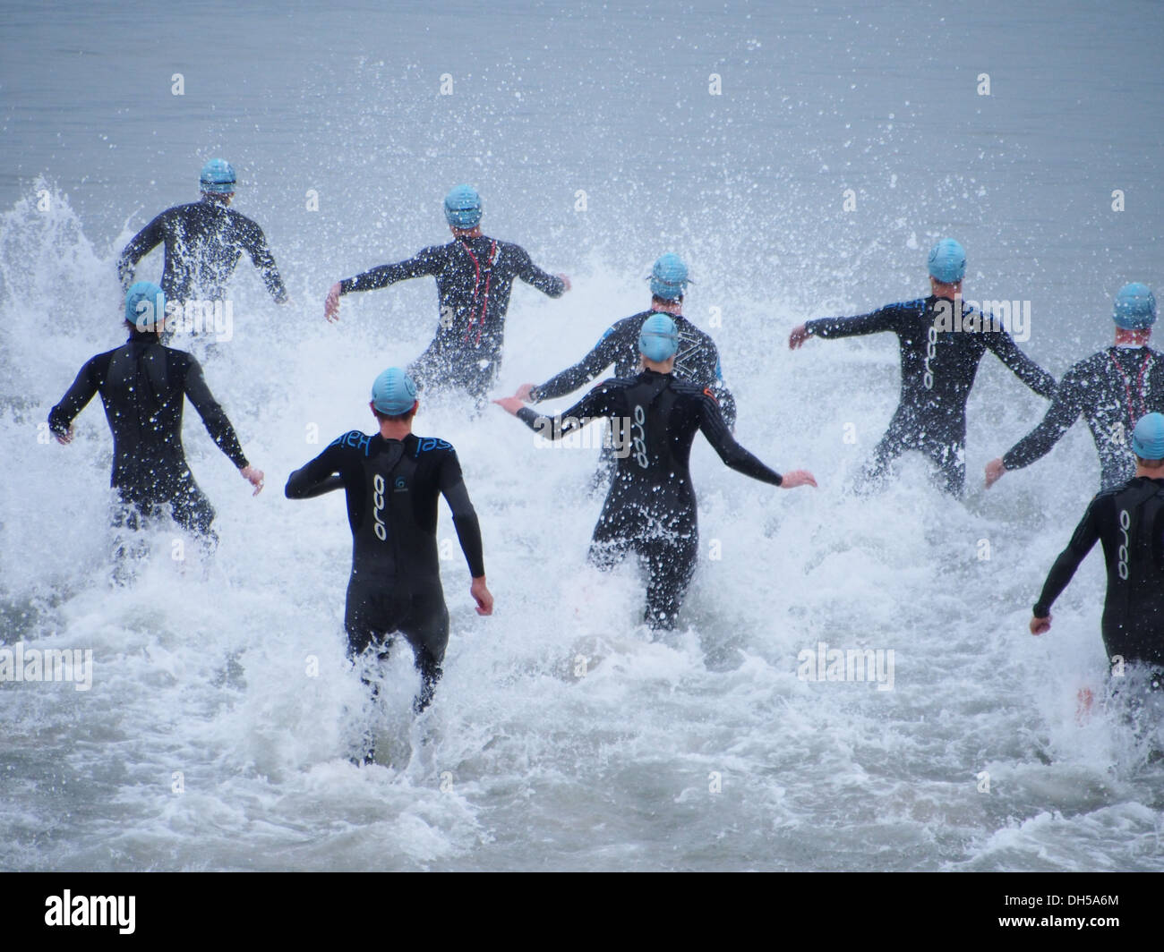 Triathletes enter the sea at the start of the Portsmouth 2013 triathlon. - Stock Image