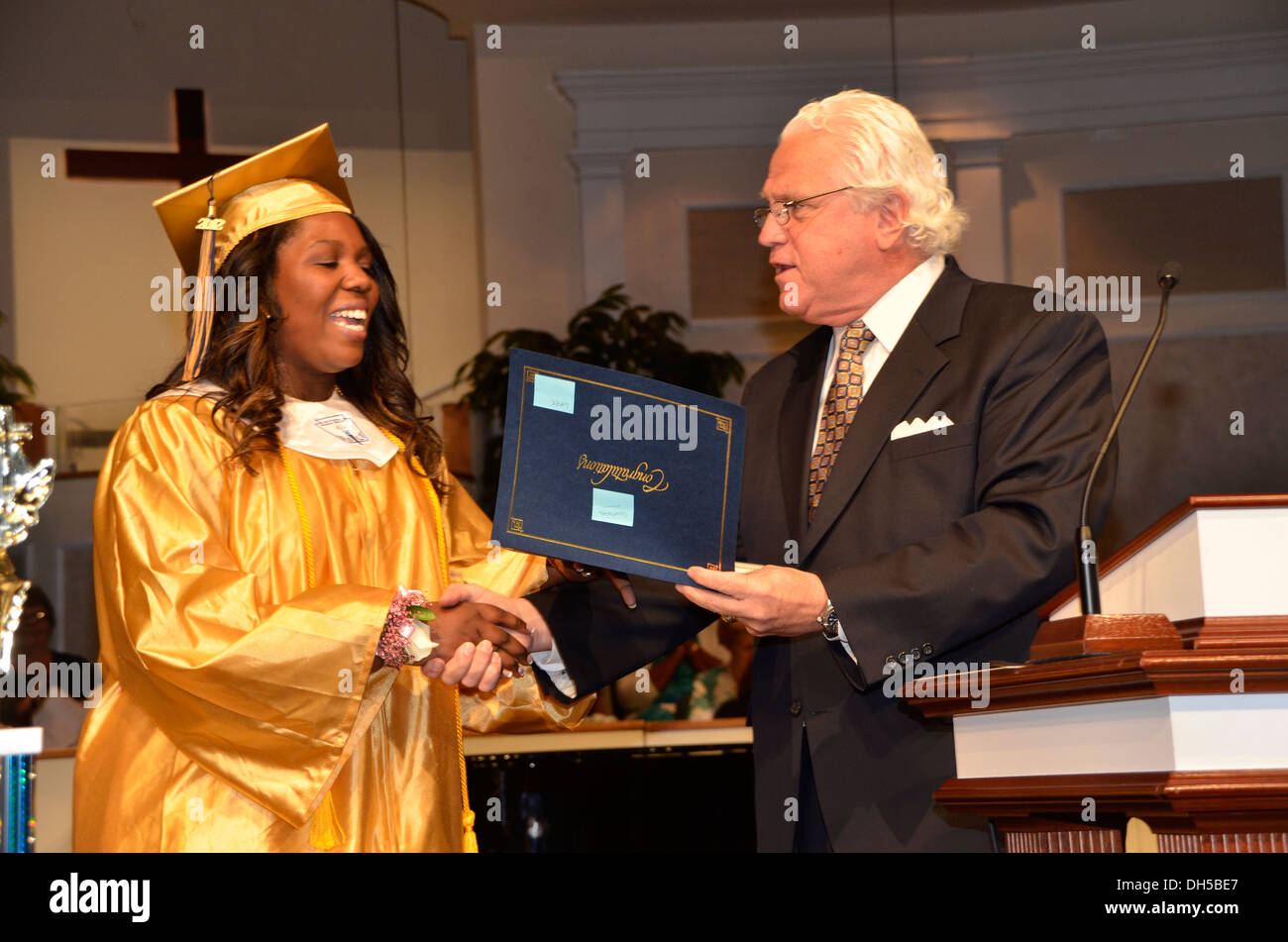 Maryland Senator Michael Miller present a diploma to a graduating student at a high school graduation, Stock Photo