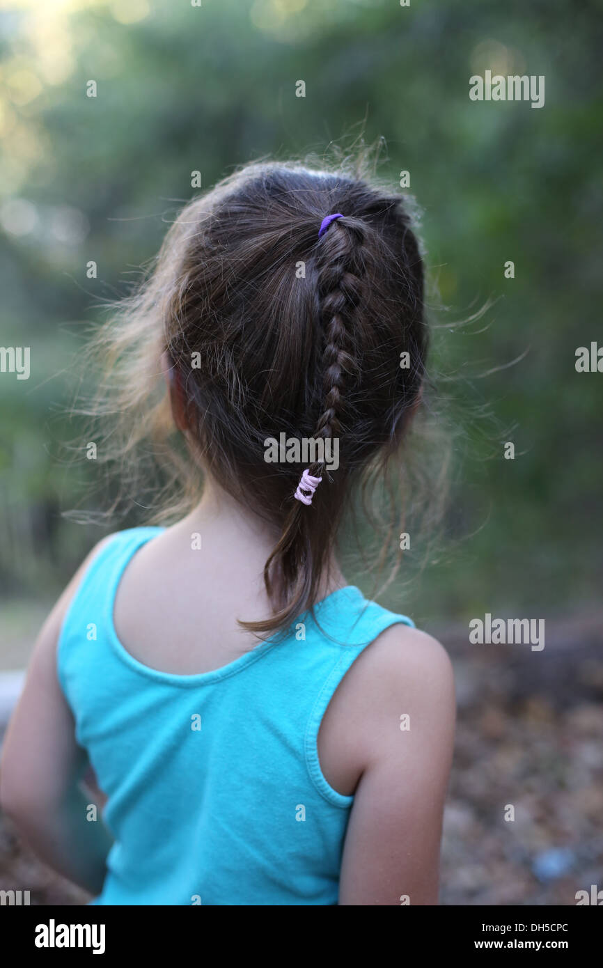 A young girl with a braided pony tail, as seen from behind. - Stock Image