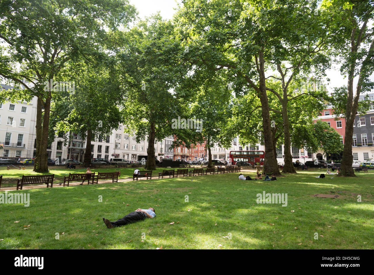 Office worker taking a rest in Berkeley Square Gardens, Mayfair, London, England, UK - Stock Image