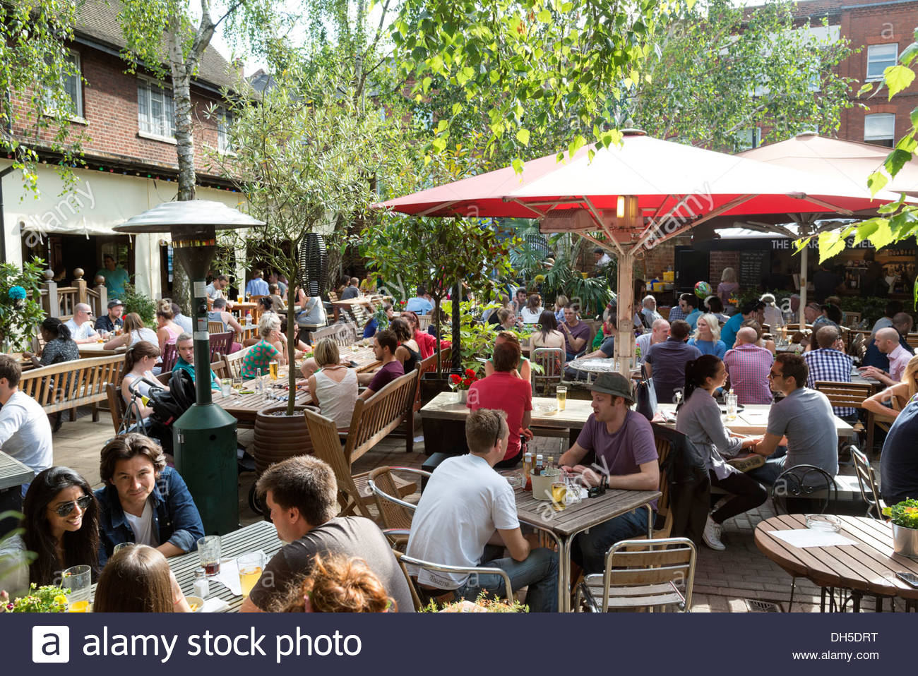 People drinking in the beer garden of The Garden Gate pub, Hampstead, London, England, UK - Stock Image