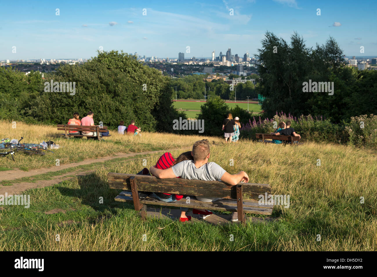 Young couple enjoying the view from a bench on Parliament Hill, Hampstead Heath, London, England, UK - Stock Image