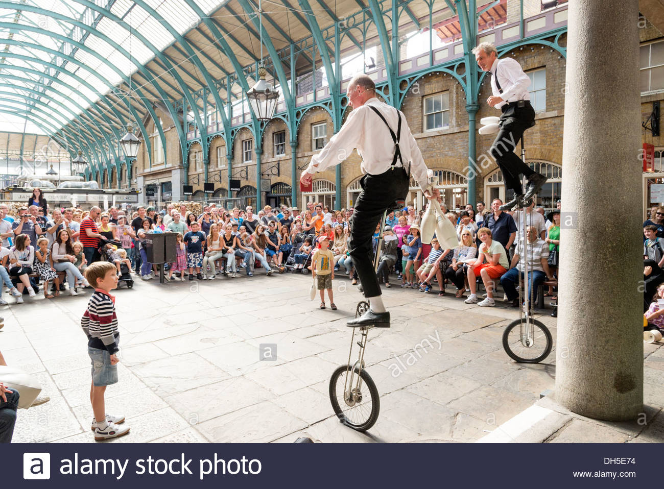Unicycle performers in Covent Garden, London, England, UK - Stock Image