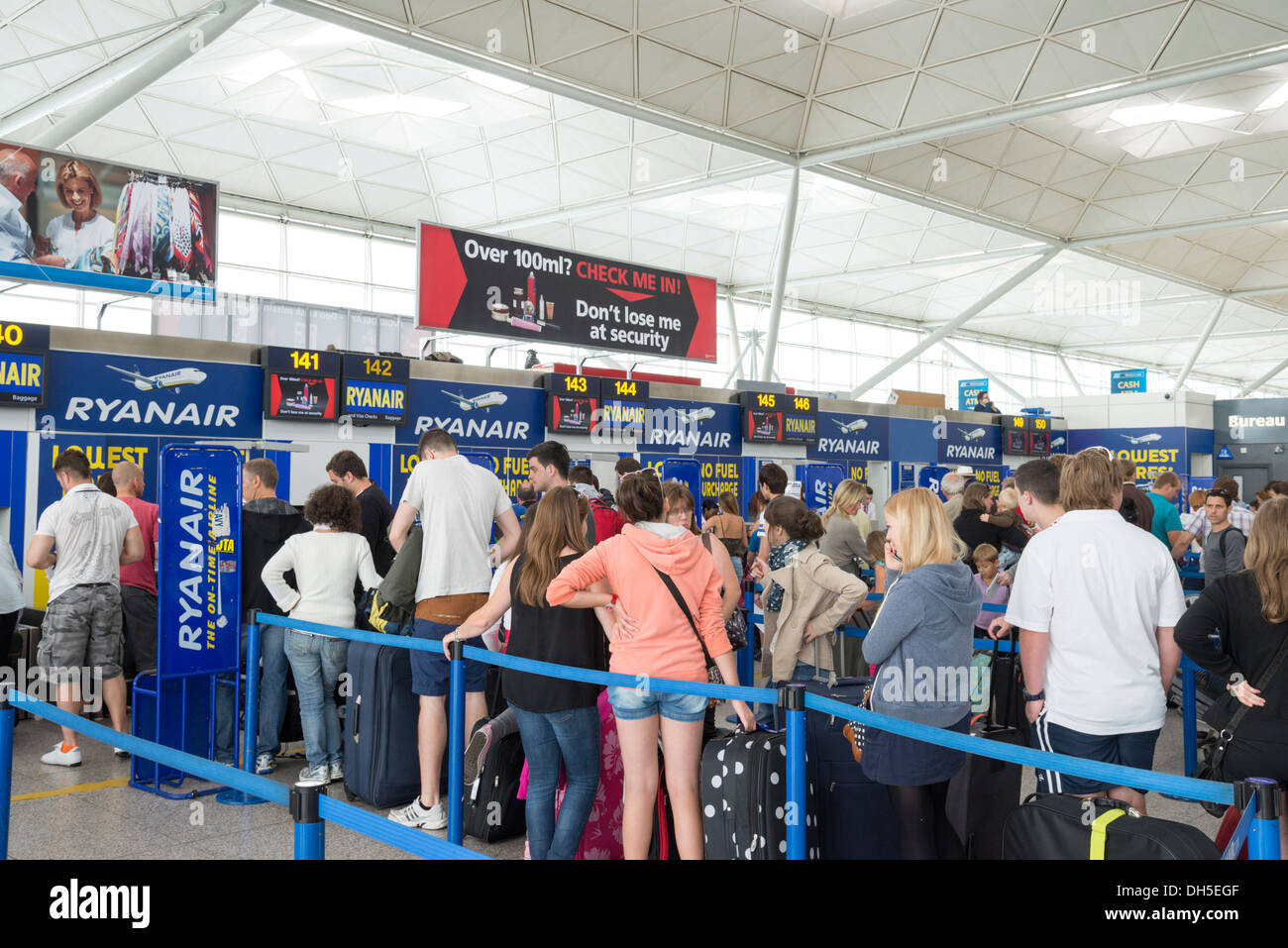 People queuing at the Ryanair check in and bag drop at Stansted Airport, England, UK - Stock Image