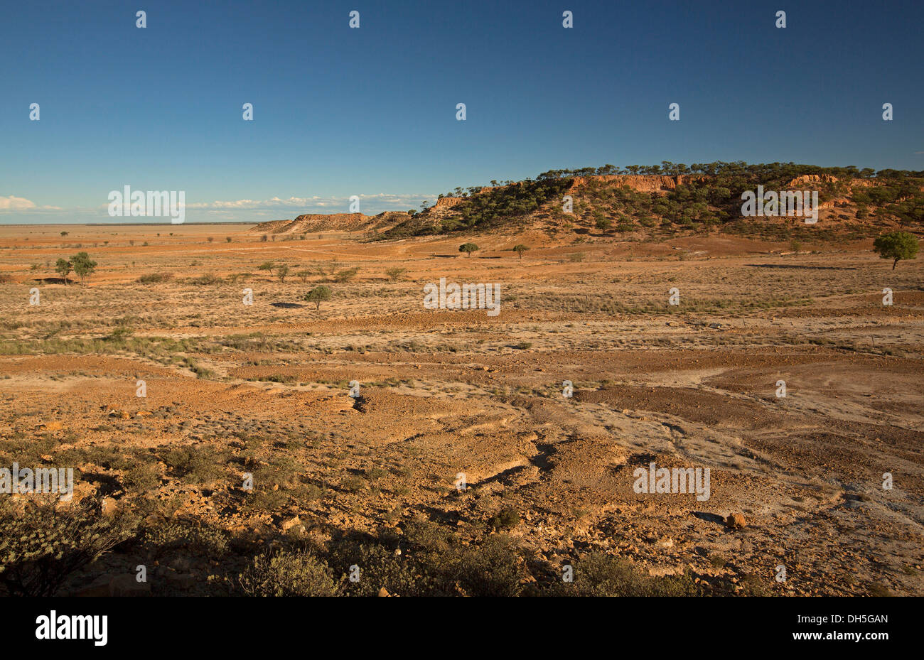 Vast barren Australian outback landscape with brown treeless plains stretching to rugged rocky Ayrshire Hills in western Queensland during drought - Stock Image